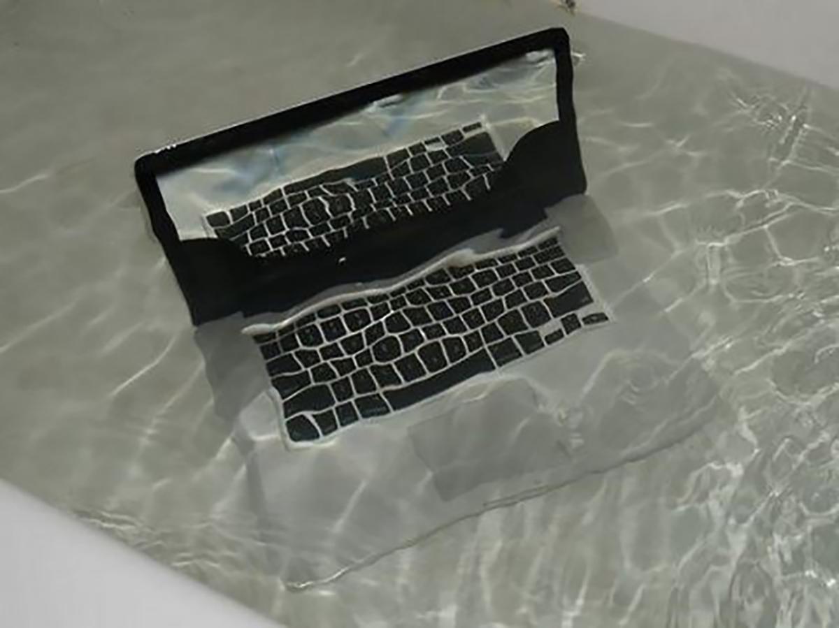 Mac laptop half-submerged in a bath.
